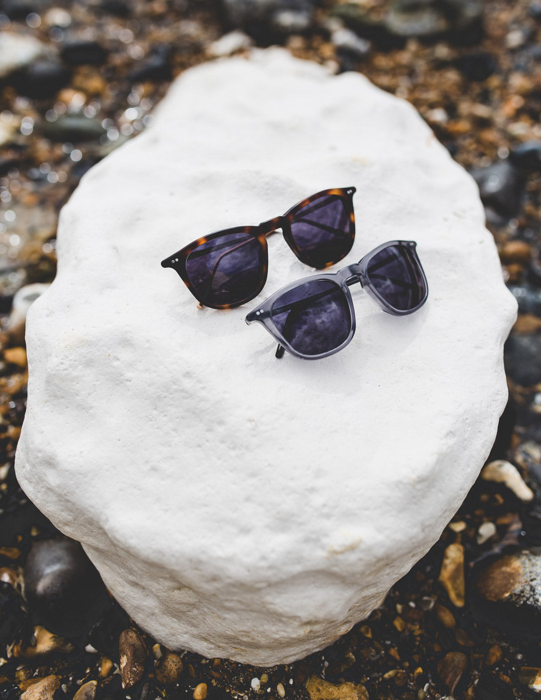 Tortoise and grey sunglasses frames sitting together on top of white rock on beach