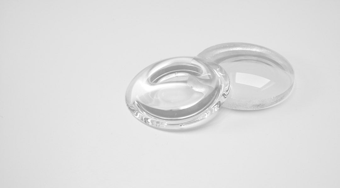 Two glasses lenses on top of each other on a white table