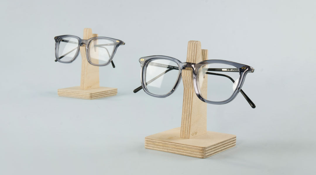 Two grey glasses on two wooden glasses holders