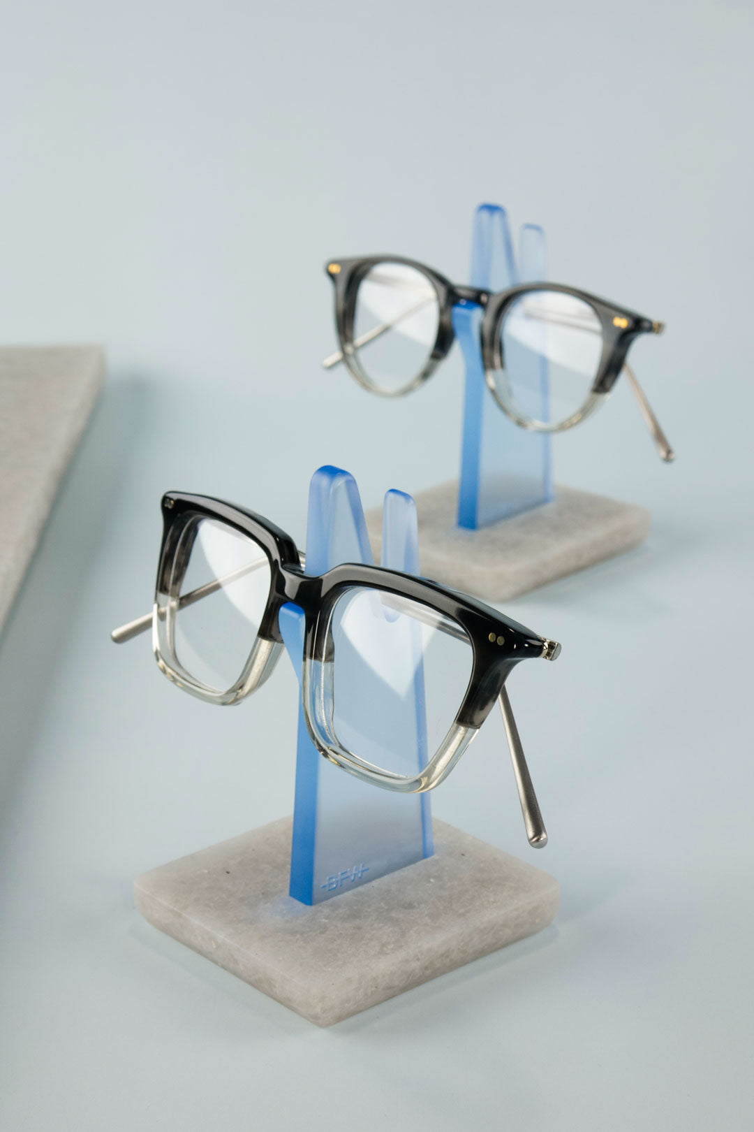 Two tone glasses frames resting on blue eyeglass holders