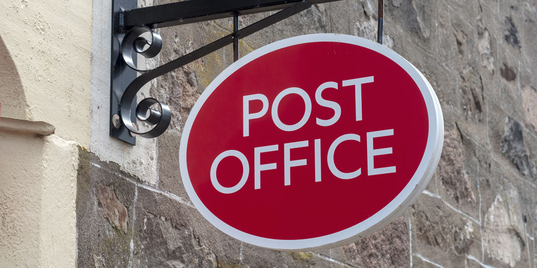 Upward view of red UK Post Office shop sign