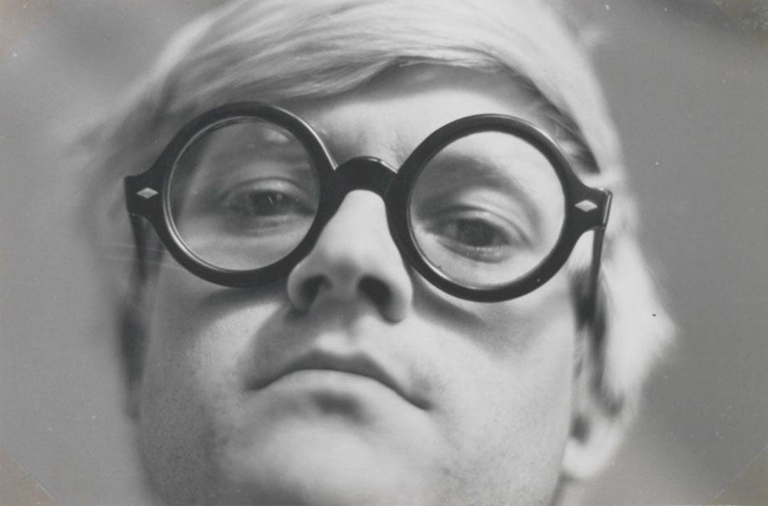 Very close view of painter David Hockney staring thorugh his thick rimmed glasses