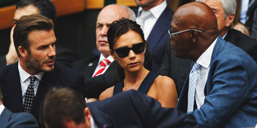 Victoria Beckham seated beside husband David Beckham at Wimbledon speaking with Samuel L Jackson