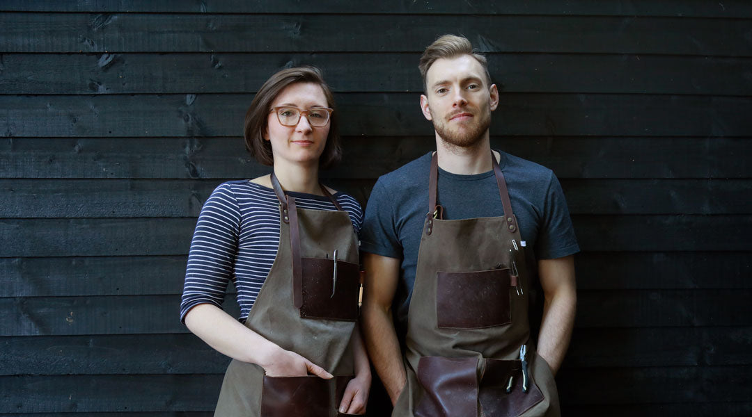 Woman and man standing outside workshop wearing aprons