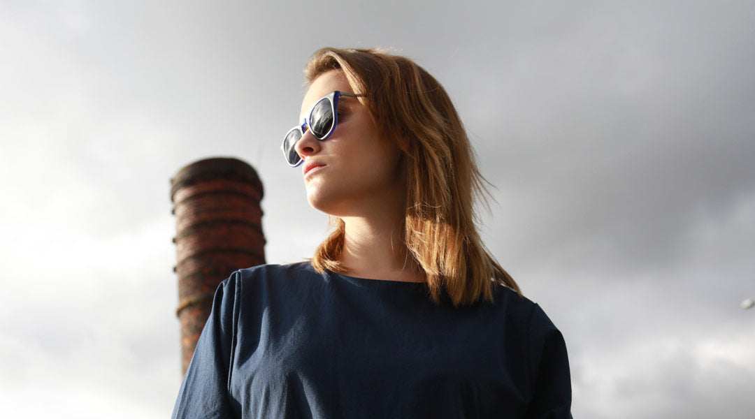 Woman looking towards the sun wearing blue sunglasses frame