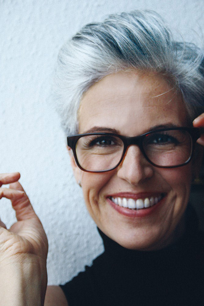 Woman smiling with grey combed hair wearing rounded eyeglasses frame
