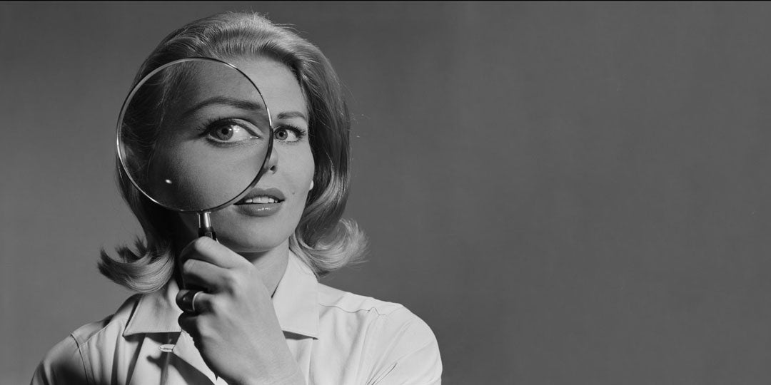 Women holding magnifying glass to her eye