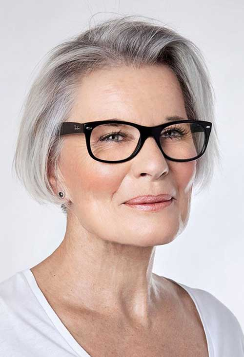 Women with short grey hair side on wearing RayBan spectacle frame and white blouse