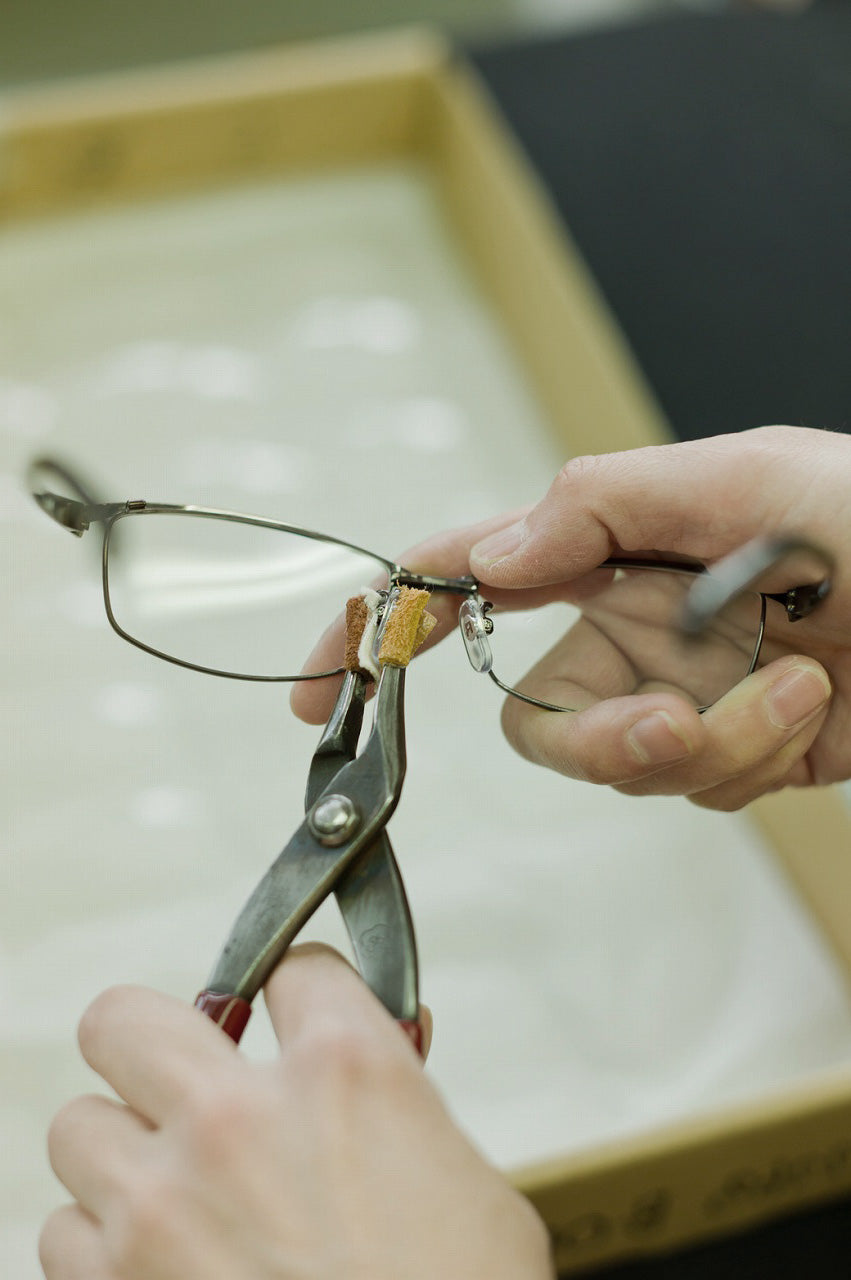 Worker adjusting the nosepads of a titanium spectacle frame using hand tools