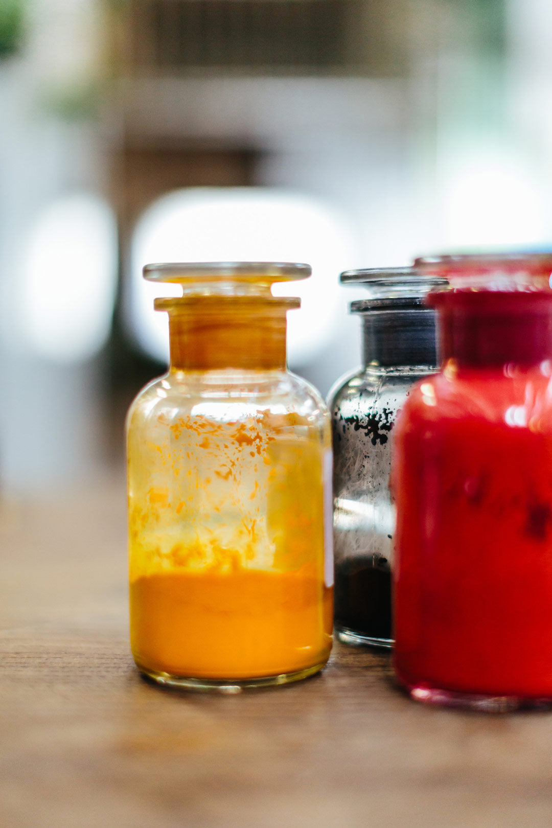 Yellow and red powdered dye inside two glass jars