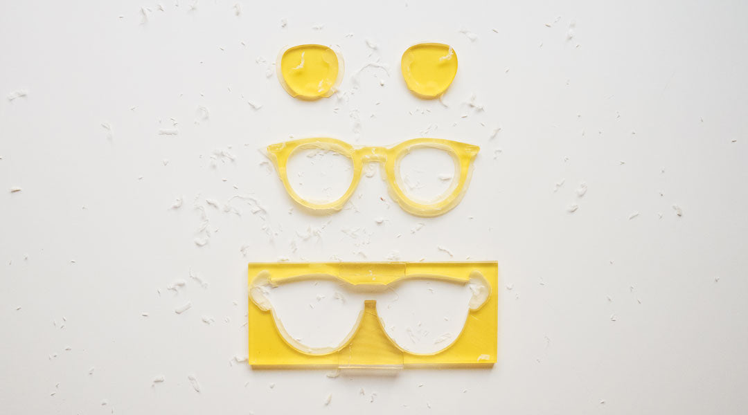 Yellow glasses design cut from acetate sheet on white table