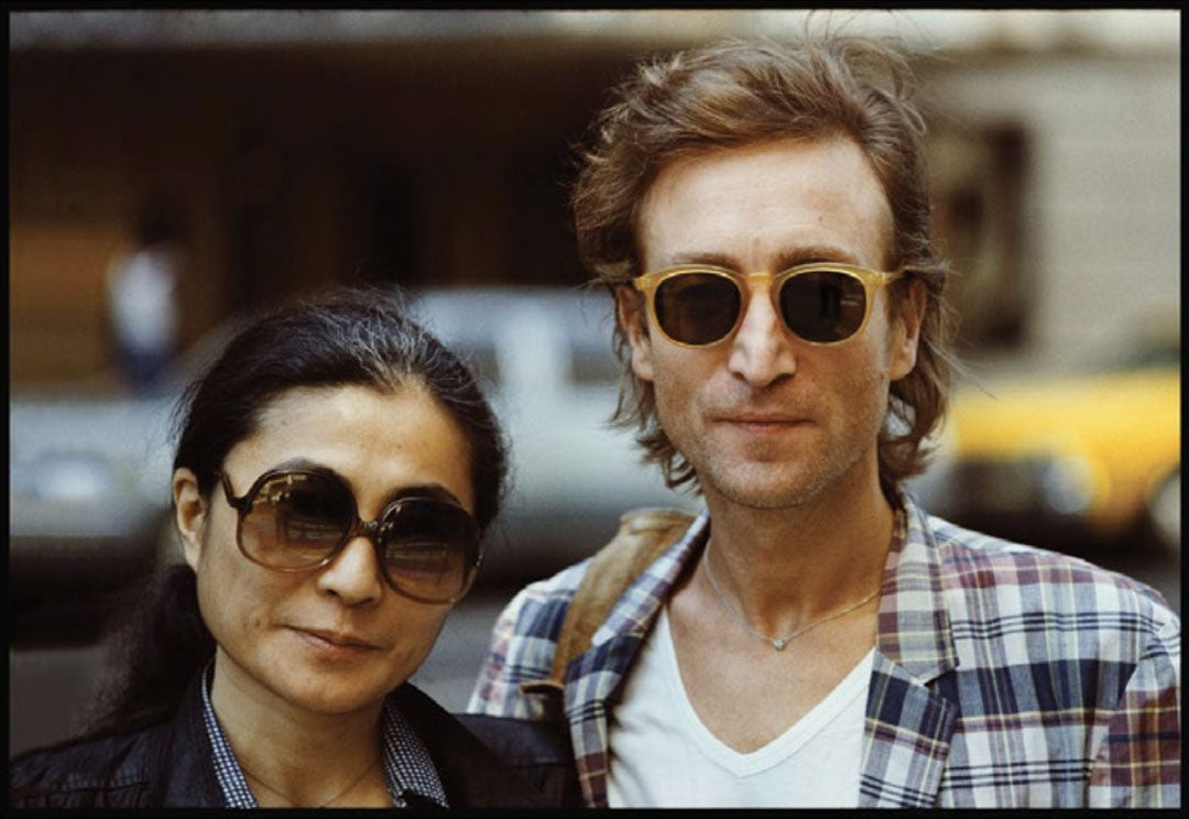 Yoko Ono and John Lennon standing together both wearing large thick sunglasses frames