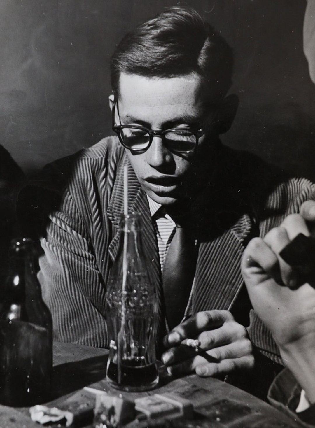 Young Dieter Rams in a Jazz club wearing thick rimmed spectacles