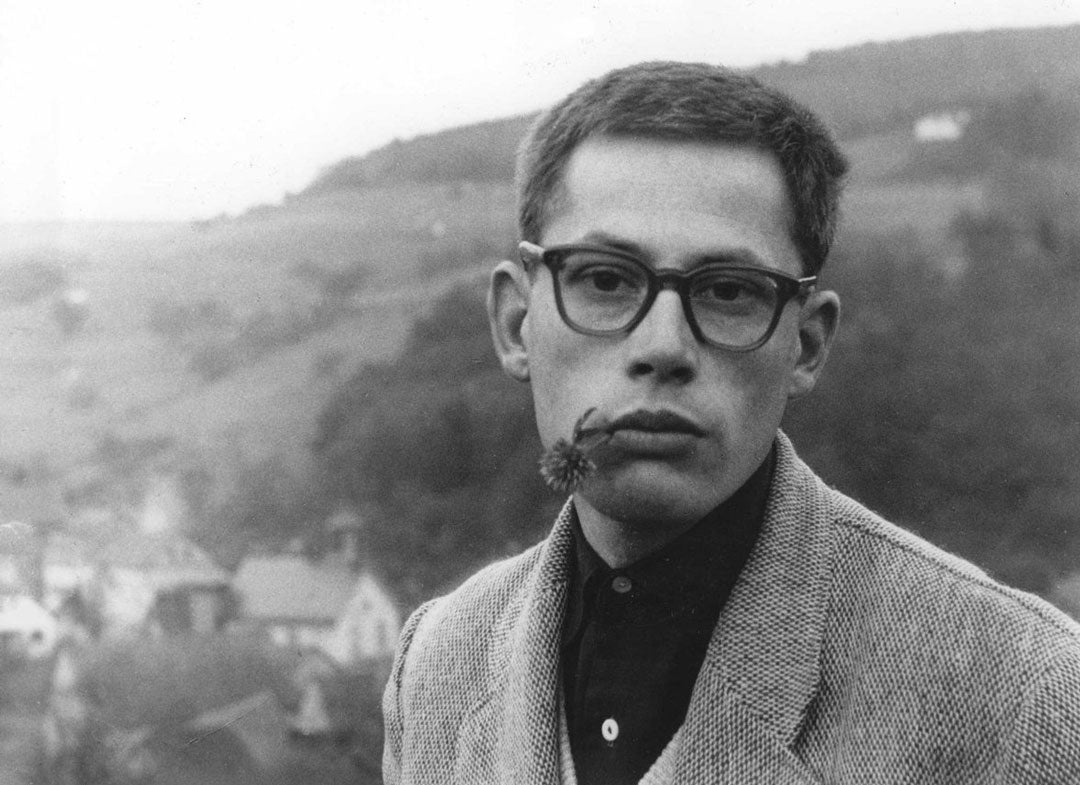 Young Dieter Rams wearing thick glasses with a flower hanging from his mouth