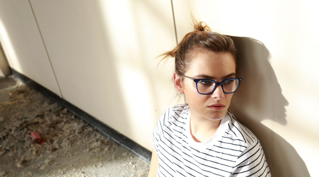 Young brunette female sitting on factory floor wearing blue spectacle frame