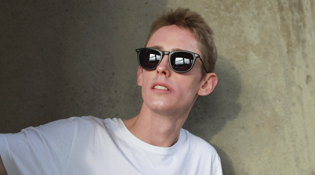 Young man wearing white Tshirt and black sunglasses frame in front of concrete wall