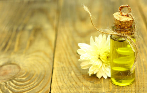 Brazil nut oil in small bottle with a flower on wood background