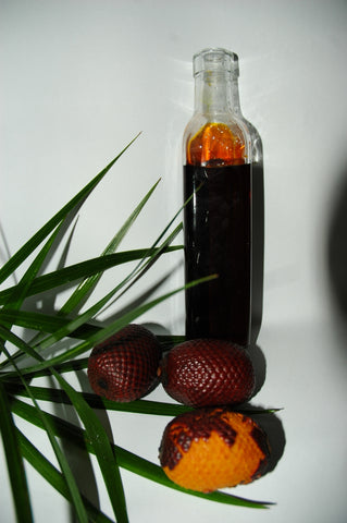 bottle of buriti oil next to buriti fruit