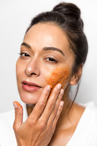 woman applies red exfoliating scrub to cheek
