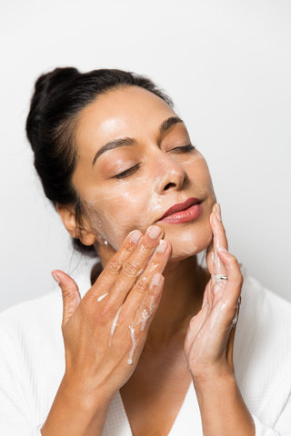woman applying white cream to face moisturize