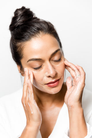 woman moisturizing face with cream