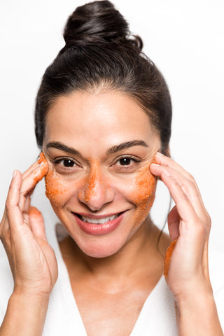 smiling woman applying red exfoliating scrub to face skincare