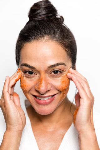 smiling woman with red exfoliating scrub on cheeks