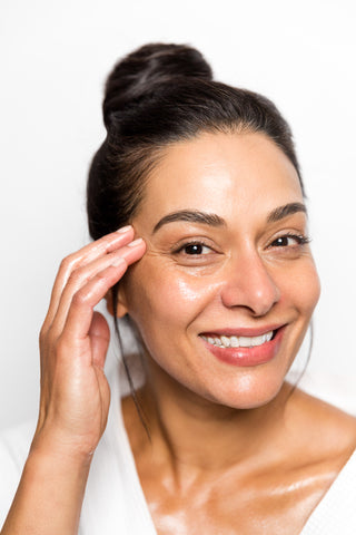 smiling woman applying moisturizing oil to face