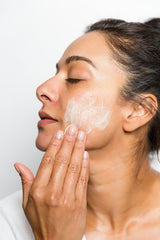 woman with eyes closed applying white skin cream to face