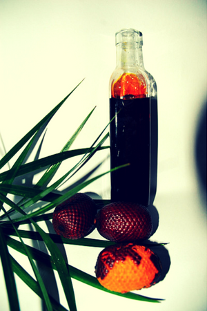 buriti oil in bottle with buriti fruit and green leaves