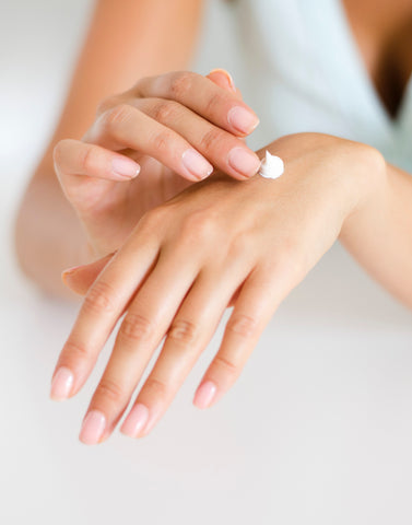 woman applying white cream to back of hand