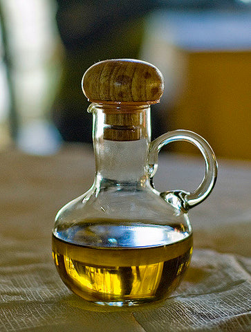 hemp oil in a glass bottle with wooden stopper on wooden table