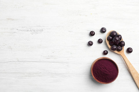 acai powder and spoonful of acai berries on distressed wood background