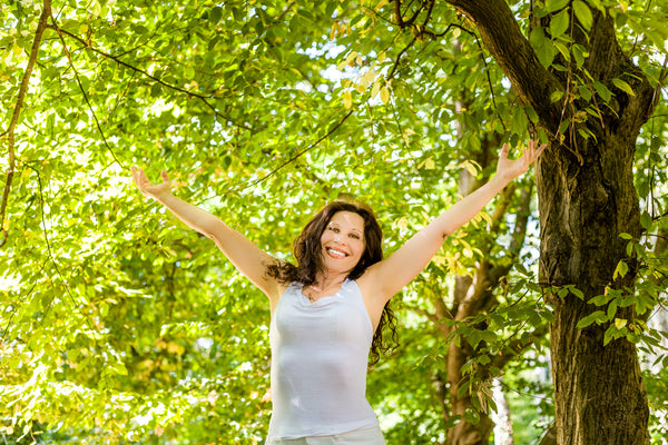 menopausal woman with outstretched arms in a park