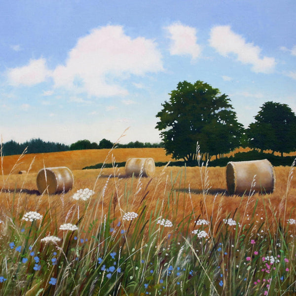 August landscape greeting card by Heather Blanchard. Round bales in field with wildflowers in foreground