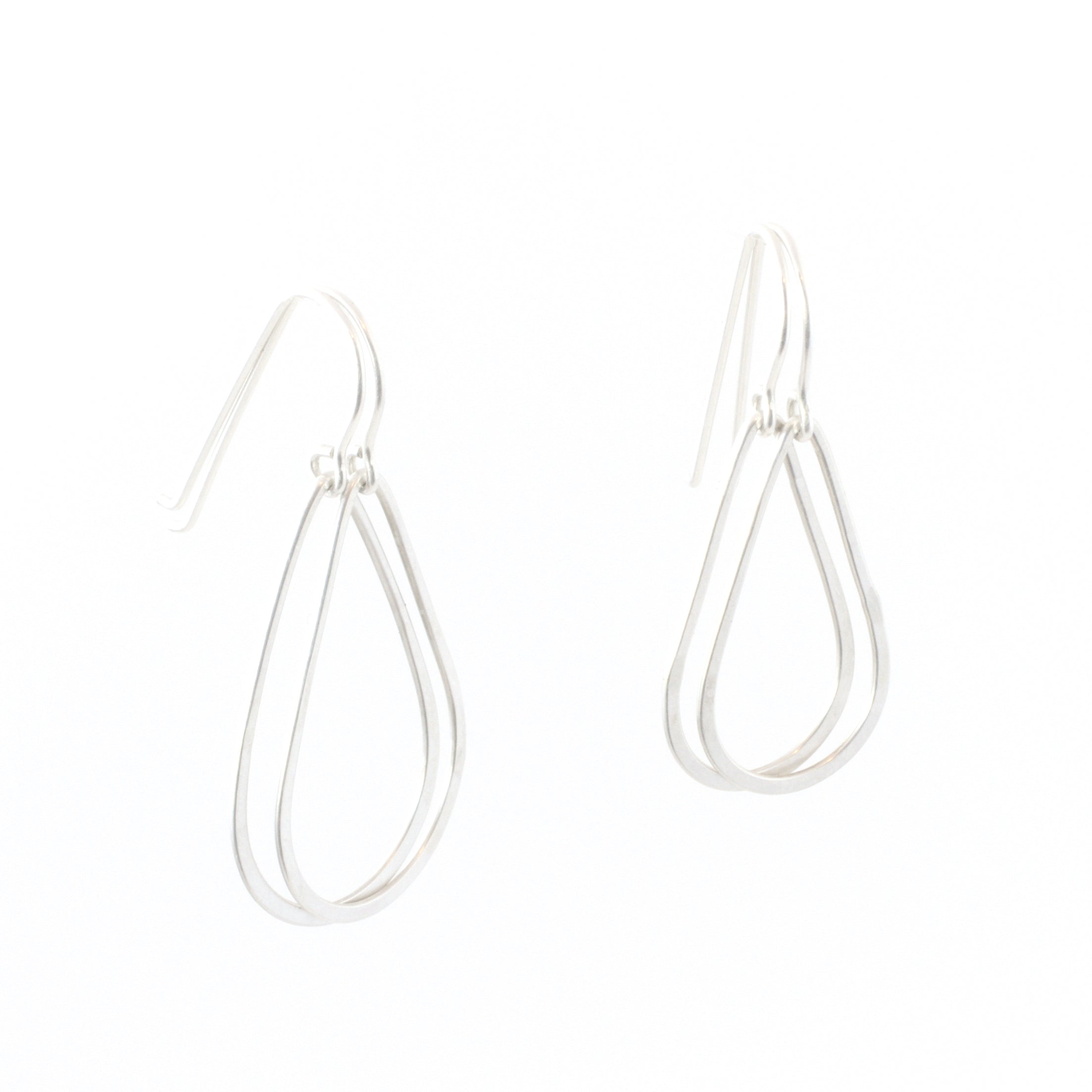 Small and large sizes of teardrop shaped earrings, hanging next to each other.