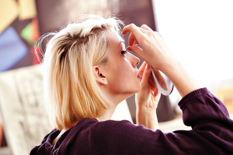 Blonde woman applying false lashes in a hand held mirror