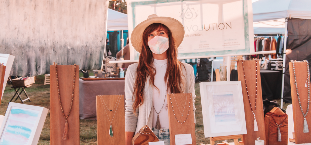 The founder of Mala Revolution stands in her pop-up shop in Venice, California where her handmade bracelets and handmade malas are displayed.  Her delicate bracelets and delicate necklaces are arranged in front of her and she smiles at the camera while wearing a mask made with original artwork.
