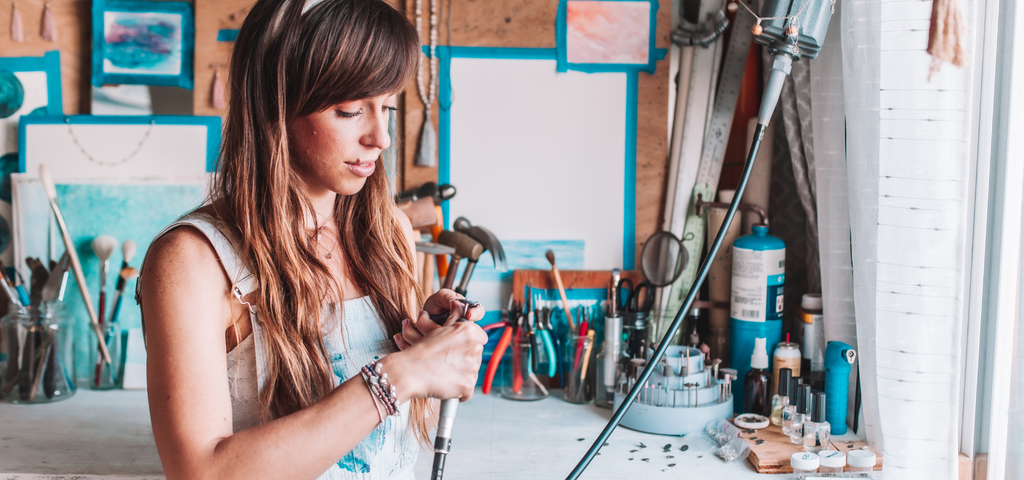 The founder of Mala Revolution in her art studio working on handmade bracelets and handmade malas and handmade jewelry.  She holds a handcrafted sterling silver charm with a lotus flower.
