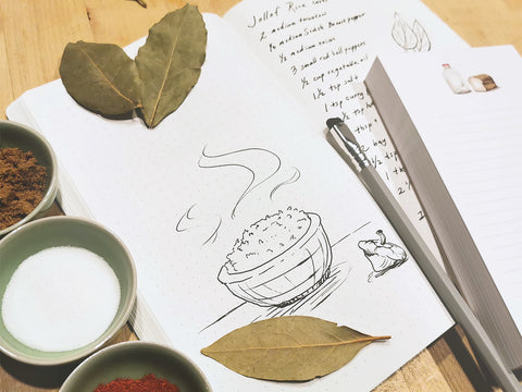 Photo of a recipe in a Stonit notebook with some bay leaves and spices