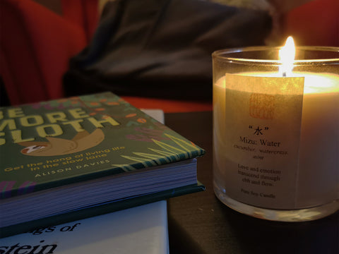 Photo of a cozy reading area with lit candle and Be More Sloth book