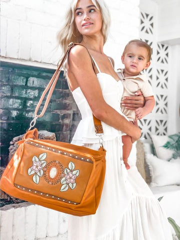 mother and baby with leather baby bag