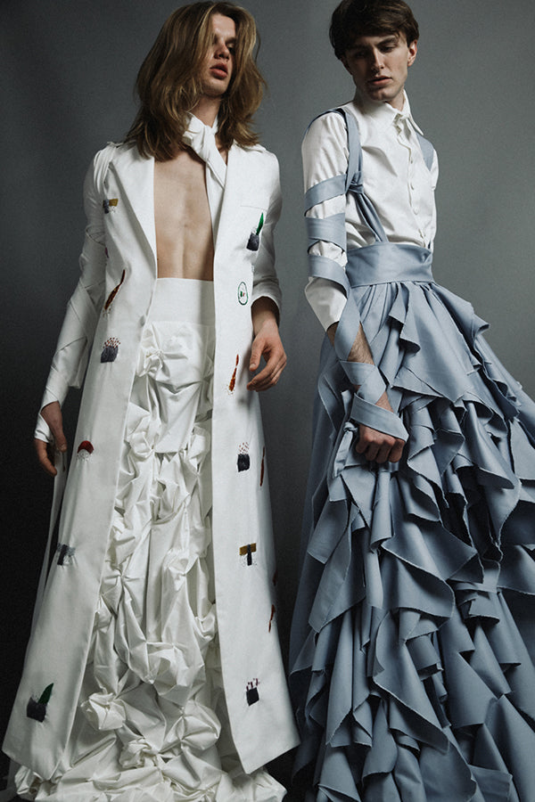 2 men wearing elegant dresses. The one on the right is a grayish-blue, the color of Bucky's eyes, and has a very ruffle-y skirt. It's long sleezed and has ribbons twined up and down the arms.