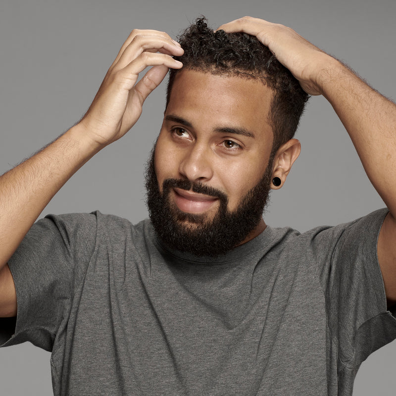 black man with a full beard and perfectly curly hair thanks to frederick benjamin grooming products, best products for black men, best products for men of color