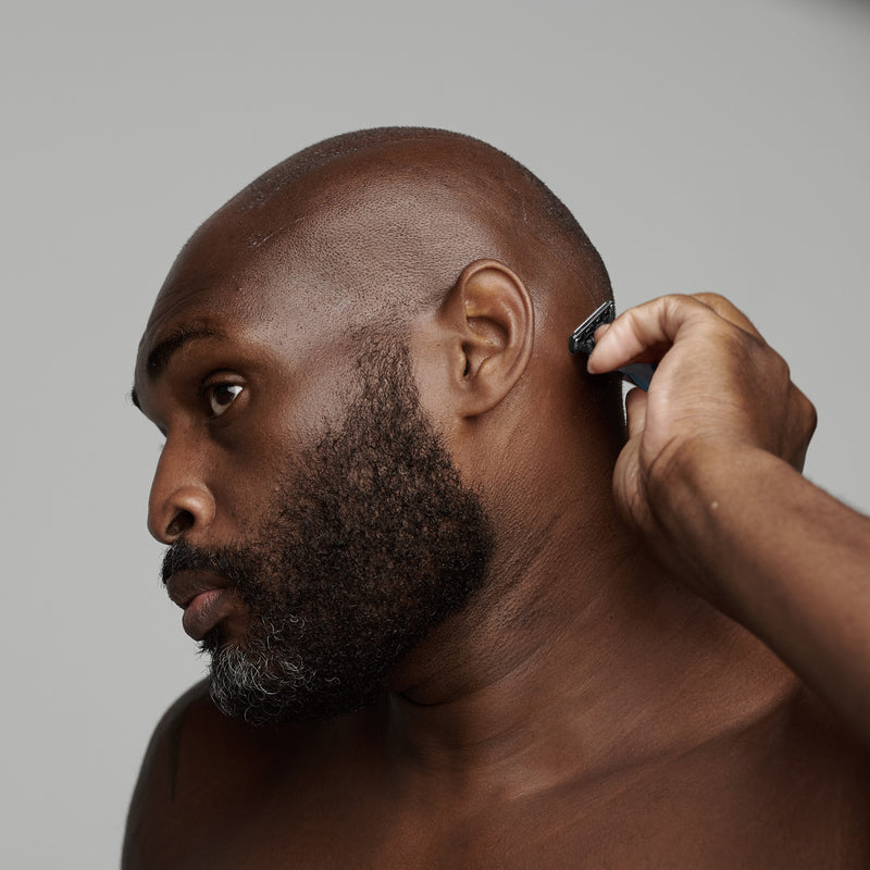 black man shaving his head with frederick benjamin shaving products