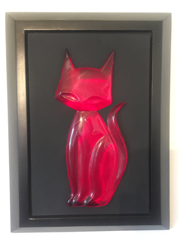 head on photo of a slightly pink-tinted red transparent kitty gem sitting upright and facing left but looking head-on, tail going up in a mild s shape kitty gem is attached to a black mat and set in a black frame.