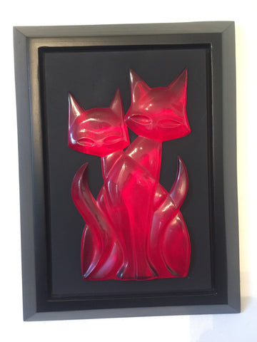 head on photo of 2 transparent red cads sitting one in front of the other facing the viewer. they form a single shape that appears to have 2 tails, one on either side. this sits on a black mat set in a black frame