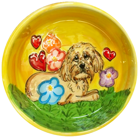 Photo of yellow ceramic dog bowl with hand painted Havanese breed dog portrait sitting in flower garden