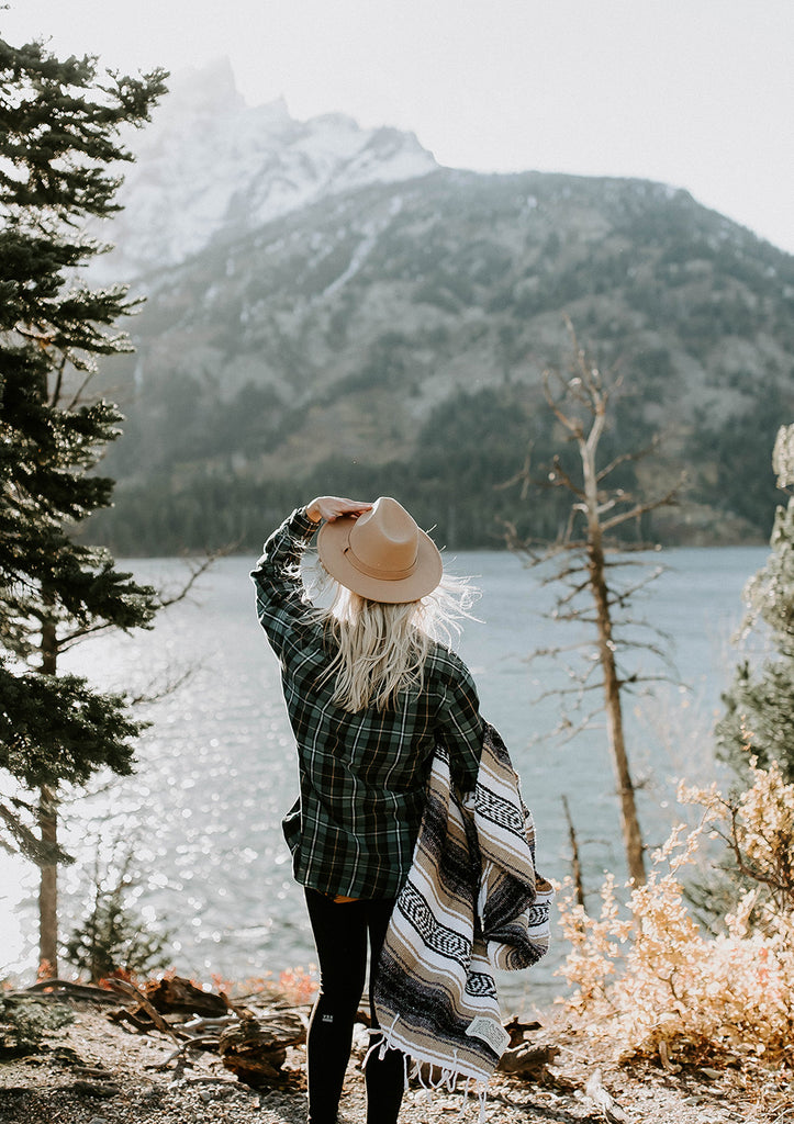 Woman overlooking a mountain with a Campo Mexican blanket. Get adventure ready with a falsa blanket of your own by Mntn & Moon