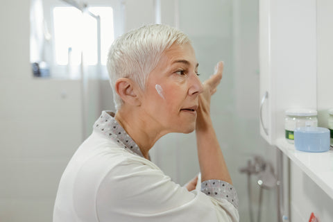 Older woman applying moisturizer to her face
